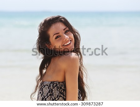 Beautiful smiling woman resting on beach on blue sea background in dress with nude shoulders - stock photo