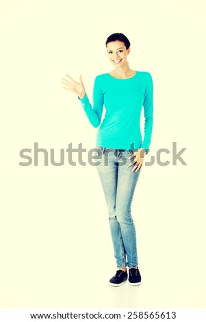 Beautiful smiling woman showing welcome gesture. - stock photo
