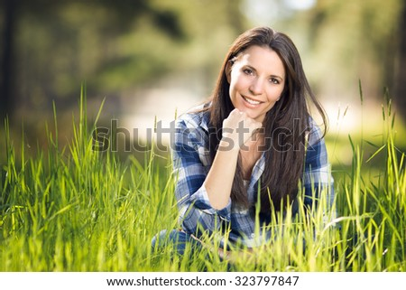 Beautiful smiling woman sitting in grass - stock photo