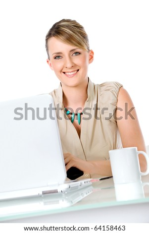 Beautiful smiling woman sitting on desk behind laptop and cup - stock photo