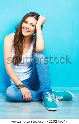 beautiful smiling woman sitting on floor against blue wall . fashion model . - stock photo