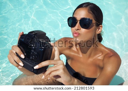 beautiful, smiling woman take a picture of herself with a digital camera in the pool. selfie, outdoors shot, horizontal - stock photo