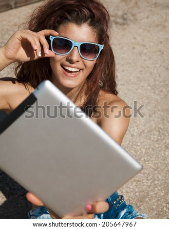 Beautiful, smiling woman take a picture of herself with digital tablet. Selfie style. Toned in warm colors. Copy space for your text. Outdoors shot, horizontal. - stock photo