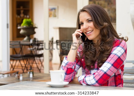 Beautiful smiling woman talking on cell phone at cafe - stock photo