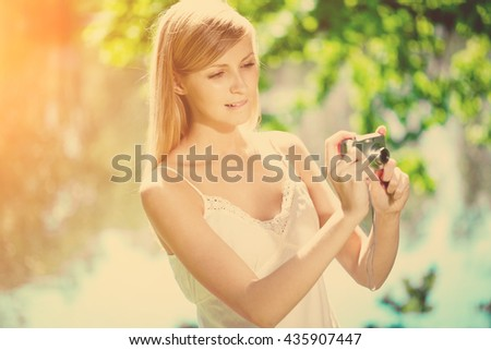 Beautiful smiling woman with a camera in her hands, outdoors  - stock photo