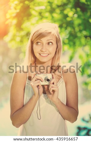 Beautiful smiling woman with a camera in his hands, outdoors  - stock photo