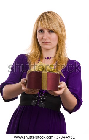 Beautiful smiling woman with a gift. Girl in purple dress is standing and holding purple box with gold ribbon on white background. Female is giving the gift.  Isolated over white background. - stock photo