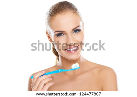 Beautiful smiling woman with bare shoulders holding a toothbrush and toothpaste, fresh studio portrait on white - stock photo