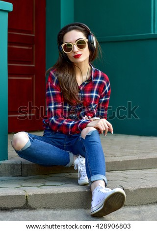 Beautiful smiling woman with headphones listens to music. Fashion woman in sunglasses outdoor. - stock photo