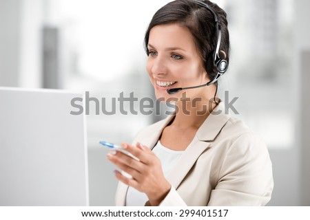 Beautiful smiling woman with headphones using laptop while searching information at call center - stock photo