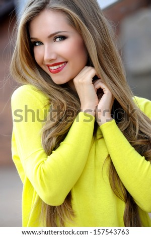 Beautiful smiling woman with long hair in a sweater outdoors - stock photo
