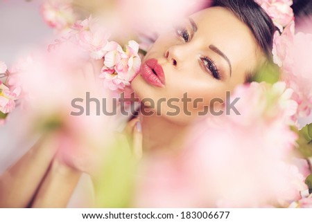 Beautiful smiling woman with spring flowers - stock photo