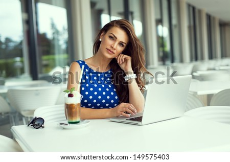 Beautiful smiling woman working on laptop - stock photo