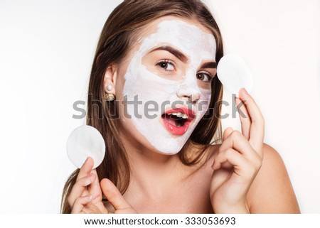 Beautiful smiling women with white clay facial mask on her face is holding cotton pads on hands - stock photo