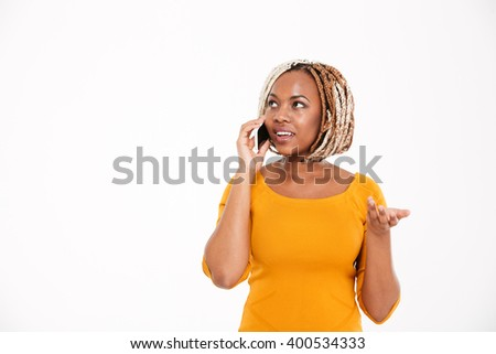 Beautiful smiling young african american woman talking on smartphone over white background - stock photo