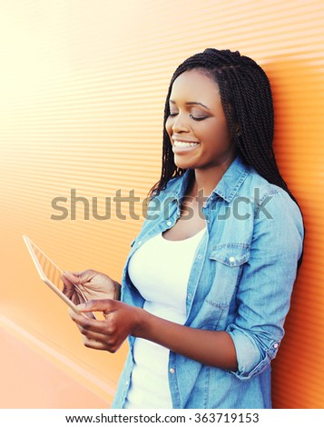 Beautiful smiling young african woman using tablet pc in city - stock photo