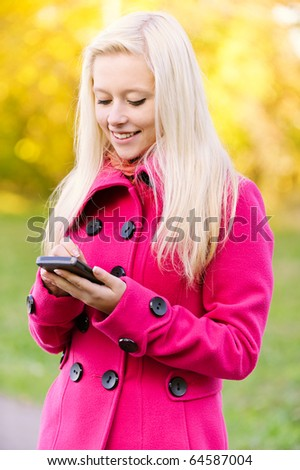 Beautiful smiling young blonde in red coat writes on pocket computer on autumn background. - stock photo