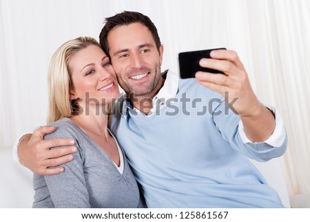 Beautiful smiling young couple photographing themselves on a mobile or smartphone posing close together with his arm around her - stock photo