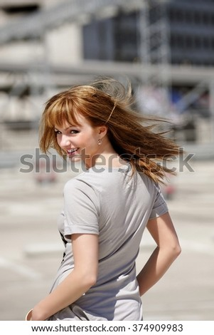 Beautiful smiling young female in summer dress walking down street and looking behind shoulder, attractive woman posing to the camera, cute girl with sexy body walking outdoors. - stock photo