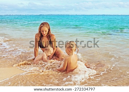 Beautiful smiling young mother with her two little cute children - boy and girl playing joyfully in sea surf on a sand beach, joy of maternity and a healthy happy family on vacation on tropical island - stock photo