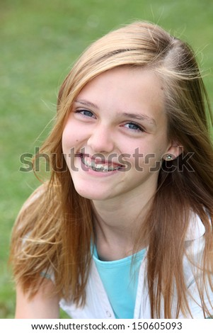 Beautiful smiling young teenager with orthodontic braces on her teeth sitting outdoors in the summer sunshine on green grass, close up head and shoulders portrait - stock photo