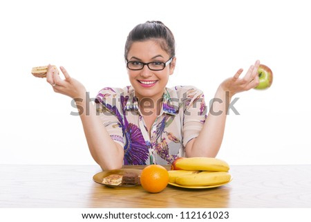 Beautiful smiling young woman choosing between healthy fruits and cakes. - stock photo