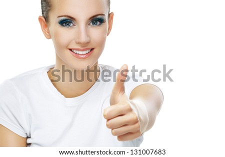Beautiful smiling young woman close-up raises thumbs up, isolated on white background. - stock photo