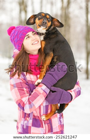 Beautiful smiling young woman holding a dog in her arms. - stock photo