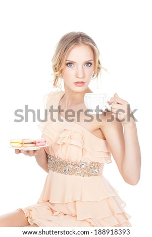 Beautiful smiling young woman holding colorful macaroons and cup of tea or coffee over white background - stock photo