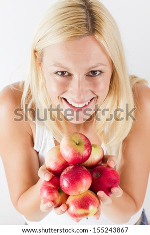 Beautiful smiling young woman holding red organic apple. - stock photo