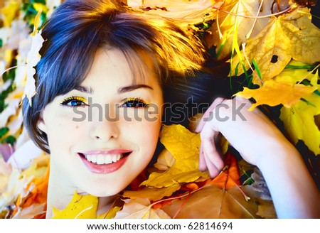 Beautiful smiling young woman in autumn leaves - stock photo