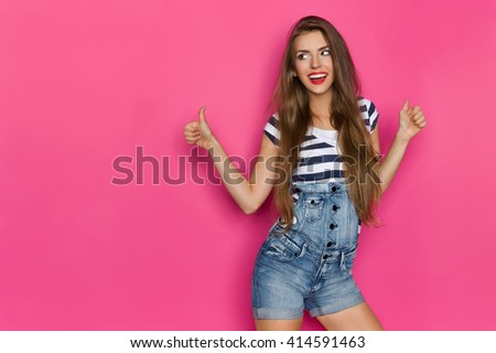 Beautiful smiling young woman in dungarees and blue striped shirt showing thumbs up and looking away. Three quarter length studio shot on pink background. - stock photo