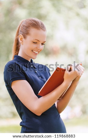 Beautiful smiling young woman reading red book, against background of summer green park. - stock photo