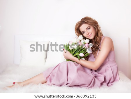 Beautiful smiling young woman sitting on a bed with a bouquet of flowers. - stock photo