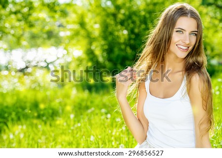 Beautiful smiling young woman sitting on a grass in the summer park. She is absolutely happy.  - stock photo