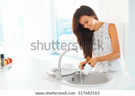 Beautiful smiling young woman washing a cup in white kitchen.  - stock photo