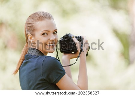 Beautiful smiling young woman with camera, against background of summer green park. - stock photo
