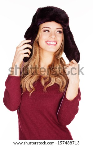 Beautiful smiling young woman with long blond hair in a winter cap holding the ear flaps in her hand isolated on white - stock photo
