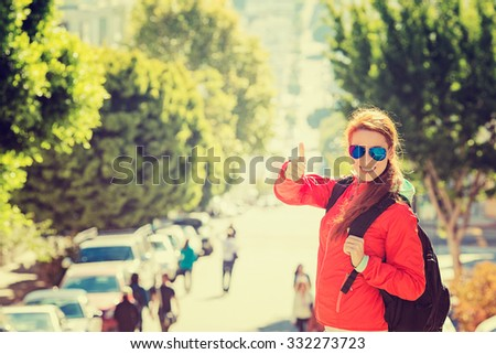 Beautiful smiling young woman with sunglasses and backpack in San Francisco city on a sunny warm autumn day. Positive emotions face expression. Instagram style yellow filter image  - stock photo