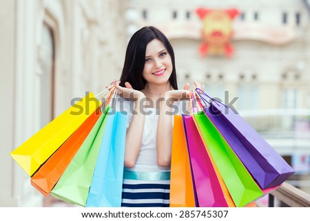Beautiful smiling young woman with the colourful shopping bags from the fancy shops. - stock photo
