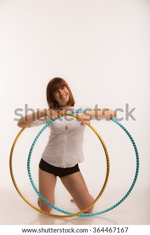 Beautiful smiling young women posing with two hula hoops in white studio background - stock photo