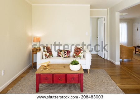 Beautiful sofa in white, with ornamented pillows framed by modern light, wooden red chest, in sumptuous style home. - stock photo