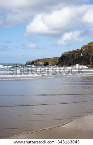 beautiful soft waves break on the beach cliffs at ballybunion - stock photo