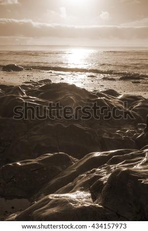 beautiful soft waves break on the rocks on sunset ballybunion beach in ireland - stock photo