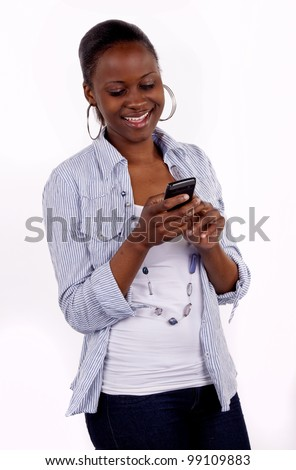 Beautiful South African woman communicating on her cell phone by text message. - stock photo