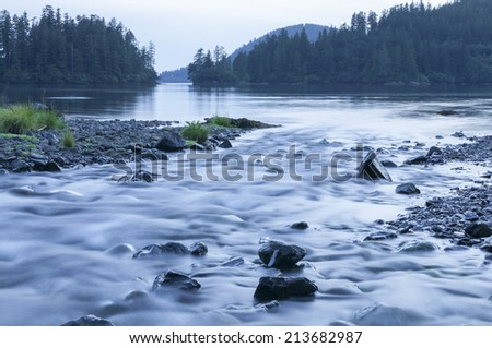 Beautiful southeast landscape at dusk featuring dreamy stream flowing into pine fringed Herring Cove on Baranof Island, Alaska - stock photo