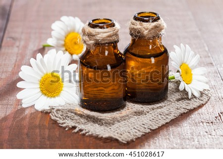 Beautiful spa and bodycare composition of fresh camomile flowers and organic oils - stock photo