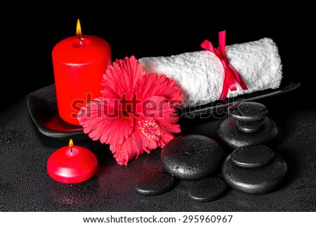 beautiful spa background of hibiscus flower with dew, red candles and white rolled towel tied with ribbon on zen stones - stock photo