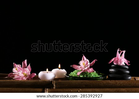 Beautiful spa composition with flowers and candles on black background - stock photo