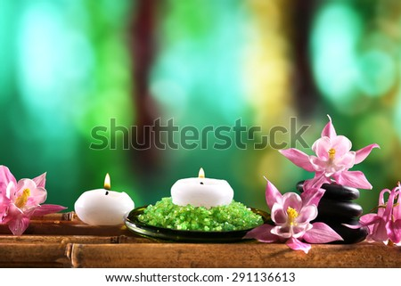 Beautiful spa composition with flowers and candles on bright background - stock photo